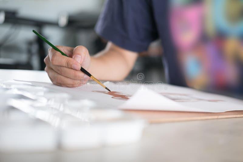 Imagem da pintura do artista no papel no estúdio Escova da terra arrendada da mulher foto de stock