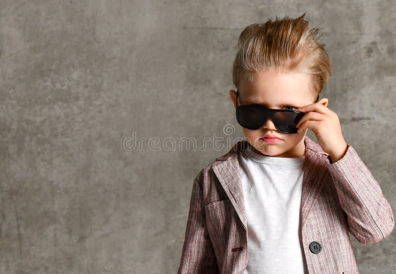 Imagem da posição entusiasmado alegre da criança do rapaz pequeno isolada sobre o muro de cimento foto de stock
