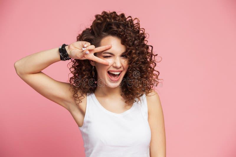 Imagem da posição feliz da jovem mulher isolada sobre o fundo cor-de-rosa que mostra o gesto da paz olhando a câmera imagens de stock