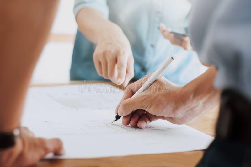 Imagem da reunião dos trabalhos de equipe do coordenador para o projeto arquitetónico em um local de trabalho imagens de stock royalty free