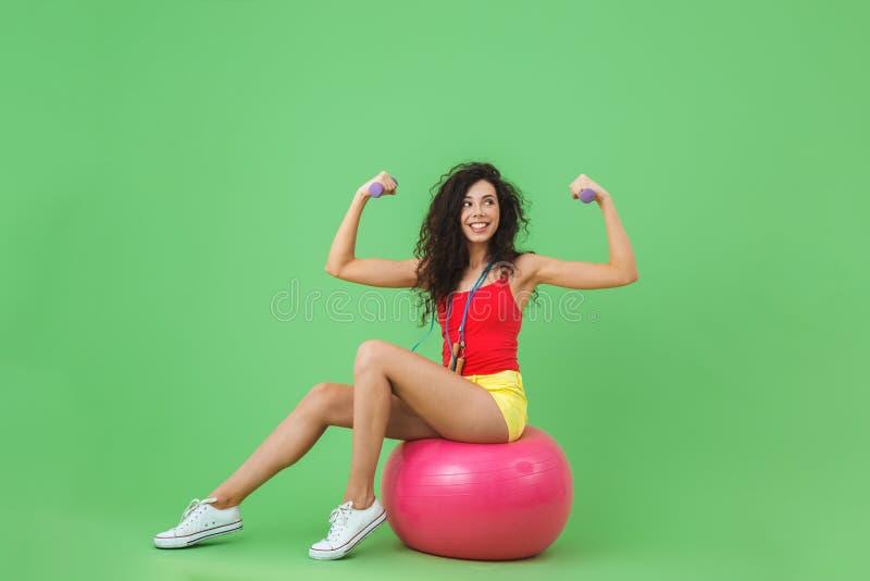 Imagem da roupa vestindo desportiva do verão da mulher 20s que levanta pesos ao sentar-se na bola da aptidão durante a ginástica  foto de stock