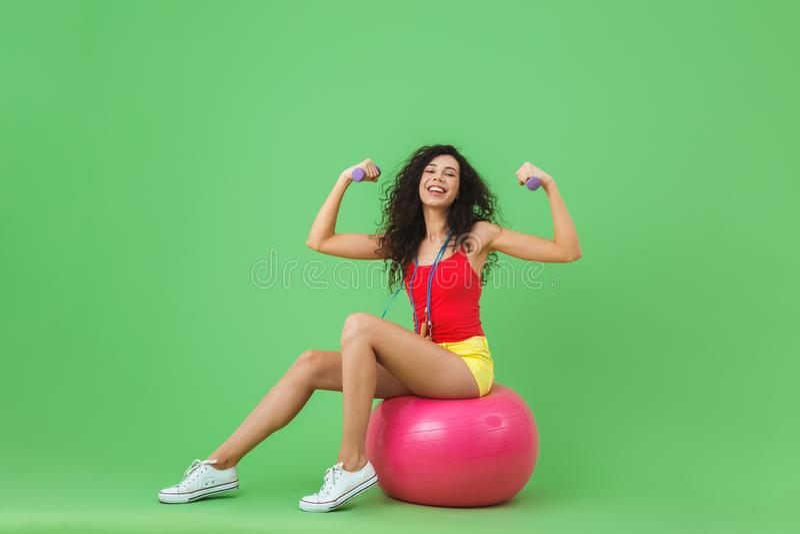 Imagem da roupa vestindo moreno do verão da mulher 20s que levanta pesos ao sentar-se na bola da aptidão durante a ginástica aeró imagem de stock royalty free