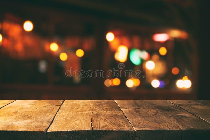 A imagem da tabela de madeira na frente do sumário borrou o fundo das luzes do restaurante foto de stock