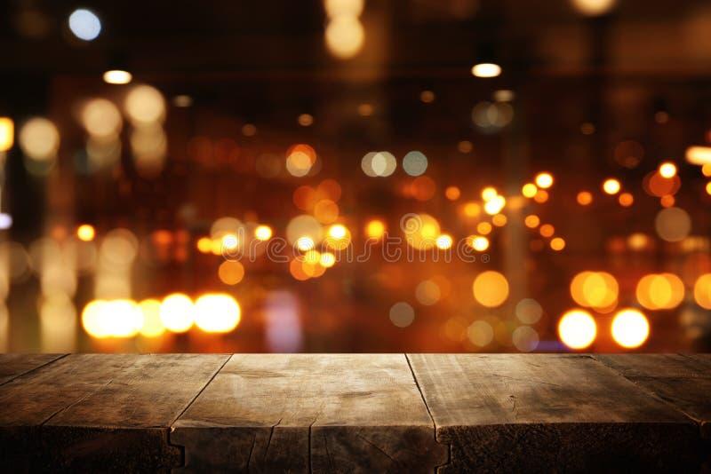 A imagem da tabela de madeira na frente do sumário borrou o fundo das luzes do restaurante imagem de stock royalty free