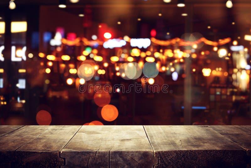 A imagem da tabela de madeira na frente do sumário borrou o fundo das luzes do restaurante fotos de stock royalty free