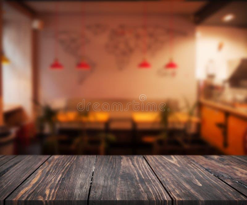 A imagem da tabela de madeira na frente do sumário borrou o fundo do interior do restaurante pode ser usada para a exposição ou a imagens de stock royalty free