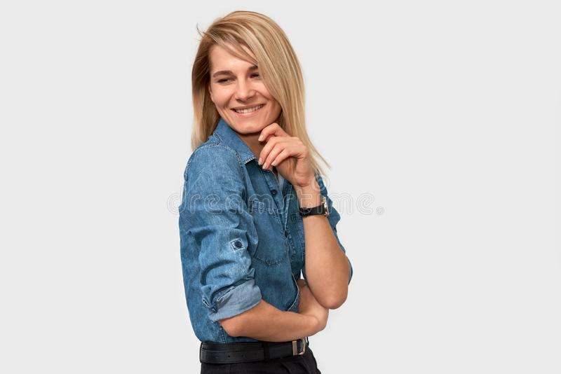 Imagem da vista lateral da mulher de negócio de sorriso europeia bonita feliz com o cabelo louro que está na camisa azul da sarja imagens de stock royalty free