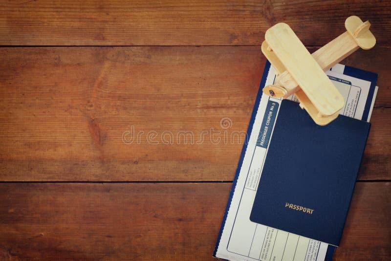 Imagem da vista superior do avião e do passaporte de madeira do bilhete do voo sobre a tabela de madeira imagens de stock