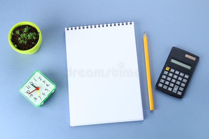 A imagem da vista superior do caderno aberto com páginas vazias e café no fundo azul, apronta-se adicionando ou zomba-se acima Ai fotografia de stock