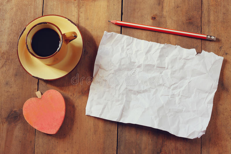 A imagem da vista superior do papel amarrotado vazio, o copo de café e o coração dão forma sobre a tabela de madeira fotografia de stock
