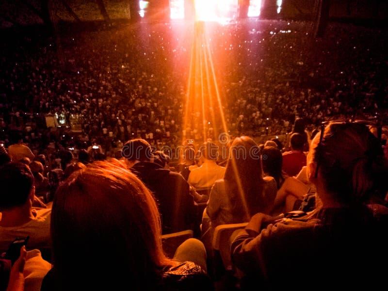 Imagem da vista traseira do concerto de observação e de escuta dos povos da música rock em tribunas da arena na noite fotos de stock royalty free