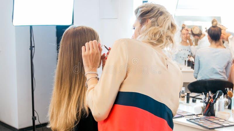 Imagem da vista traseira do maquilhador profissional que trabalha no salão de beleza foto de stock