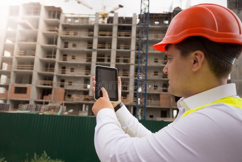 Imagem da vista traseira do trabalhador masculino da construção que usa a tabuleta digital no canteiro de obras foto de stock