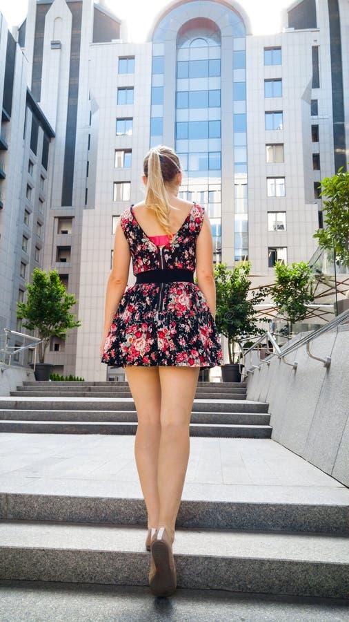 Imagem da vista traseira da jovem mulher bonita com os pés longos que vestem o vestido curto que anda acima das escadas de pedra  fotos de stock