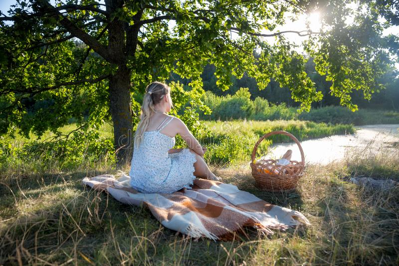 Imagem da vista traseira da jovem mulher no vestido do verão que senta-se sob a árvore grande e que olha o por do sol fotografia de stock royalty free