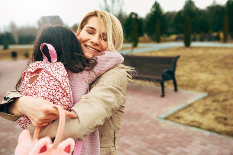 Imagem da vista traseira da mãe bonita feliz que abraça sua criança bonito da menina fora Jovem mulher de amor e sua filha de sor imagem de stock