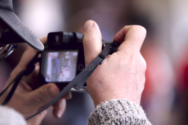 A imagem das mãos masculinas com uma câmera imagem de stock royalty free