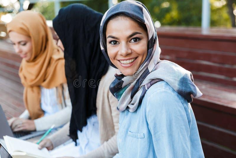 Imagem das mulheres muçulmanas dos estudantes das irmãs dos amigos felizes que sentam-se fora imagem de stock