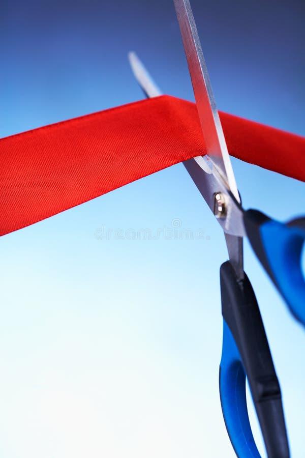 Imagem das tesouras que cortam uma fita vermelha fotografia de stock