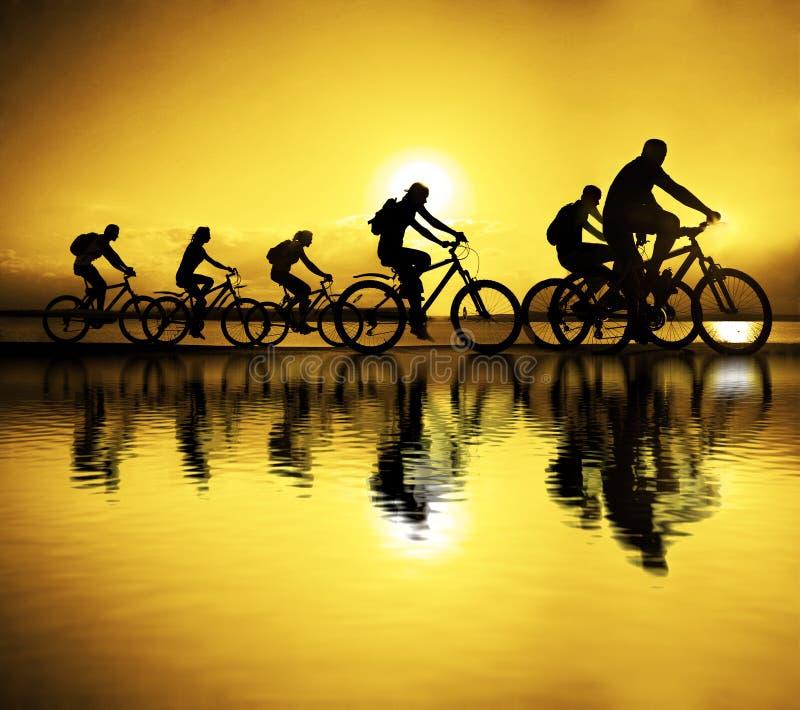 Imagem de amigos desportivos da empresa em bicicletas fora contra o sol fotos de stock royalty free
