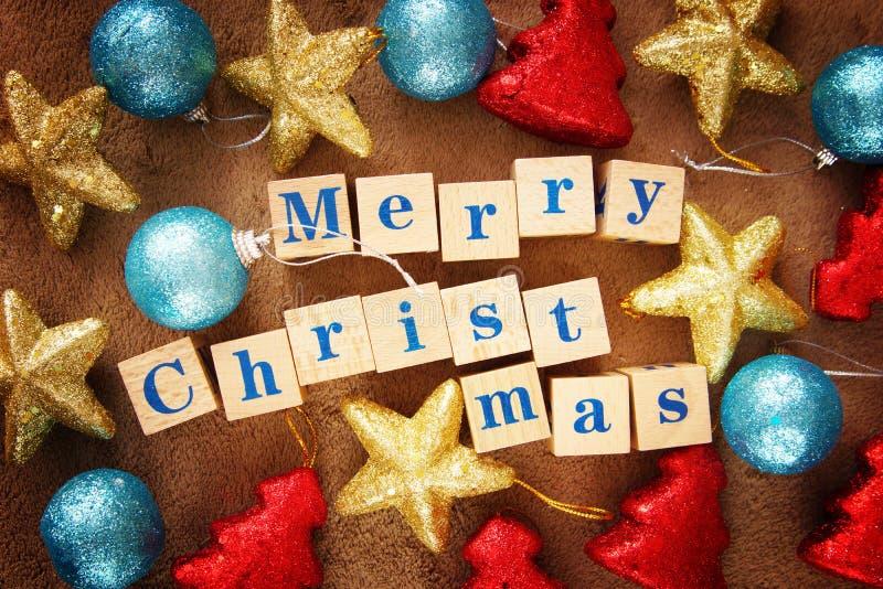 Imagem de cumprimento festiva do Feliz Natal vívido com um texto em cubos de madeira e em brinquedos coloridos foto de stock