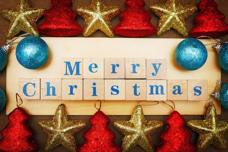 Imagem de cumprimento festiva do Feliz Natal vívido com um texto em cubos de madeira e em decorações coloridas foto de stock royalty free