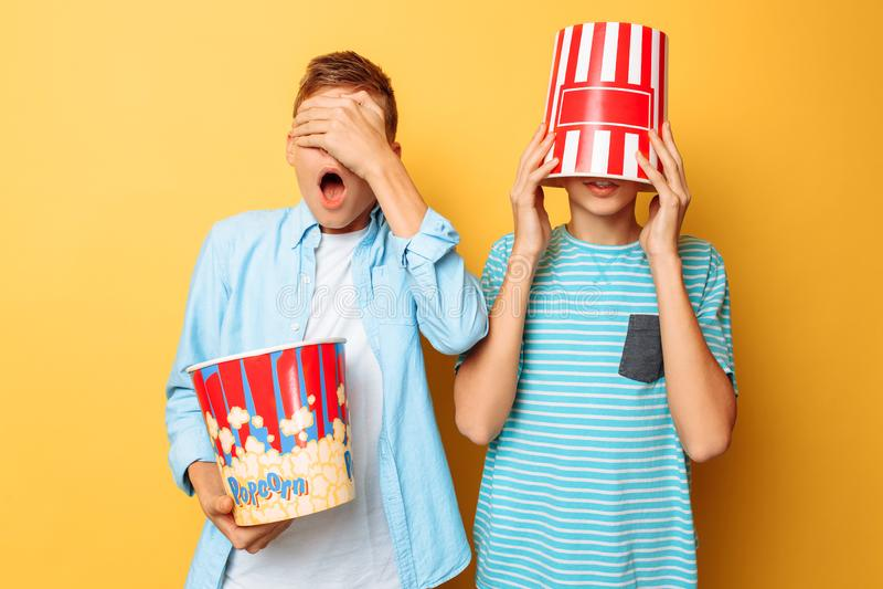 Imagem de dois adolescentes amedrontados, indivíduos que olham um filme de terror e que escondem atrás de uma cubeta da pipoca em fotografia de stock royalty free
