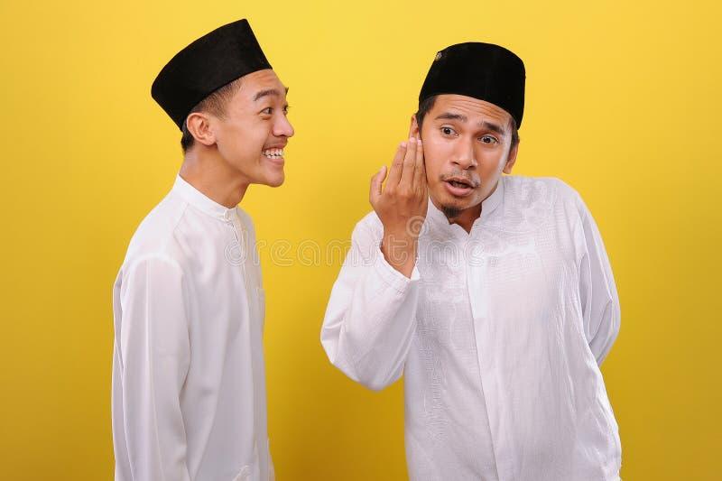 Imagem de Dois Jovens Muçulmanos Asiáticos em tecido muçulmano, sussurrando segredos ou fofocas um para o outro foto de stock