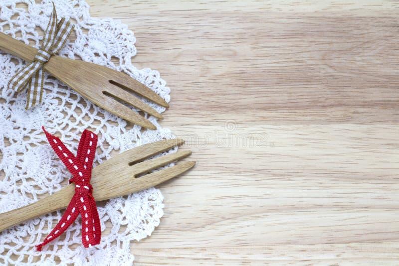 Imagem de duas forquilhas com fita e do doily branco com fundo de madeira foto de stock