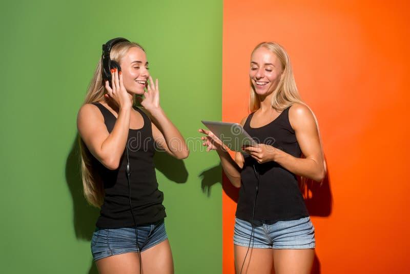 Imagem de duas mulheres felizes novas que olham a câmera e que guardam o portátil foto de stock royalty free