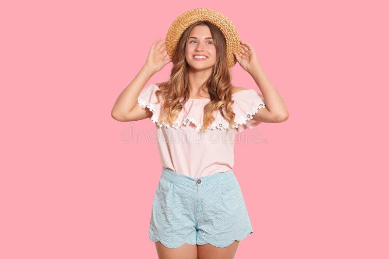 Imagem de encantar a mulher europeia adorável que toca em seu chapéu de palha com ambas as mãos, olhando de lado, o short e a blu foto de stock