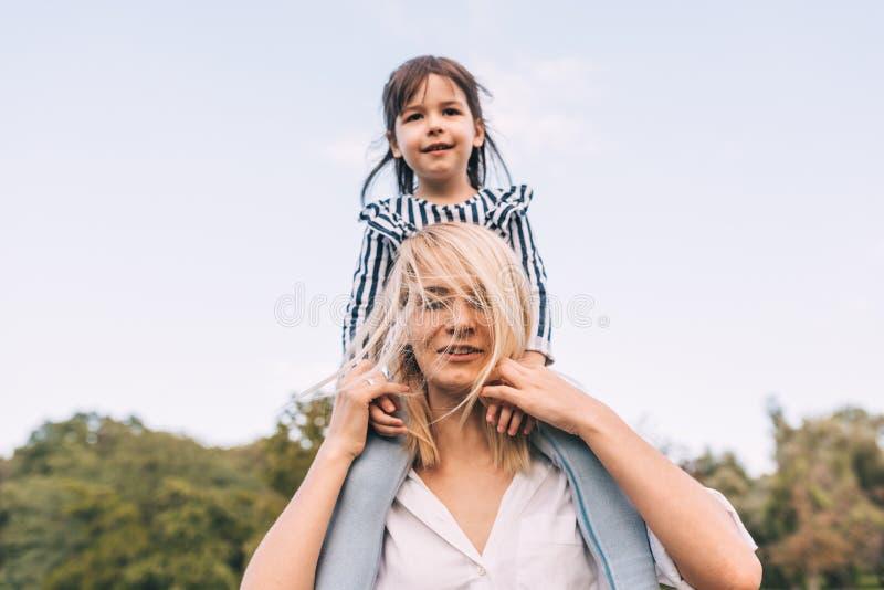 Imagem de feliz bonito pouca filha em um passeio do reboque com sua mãe de sorriso no fundo da natureza Mulher de amor e seu pouc imagem de stock