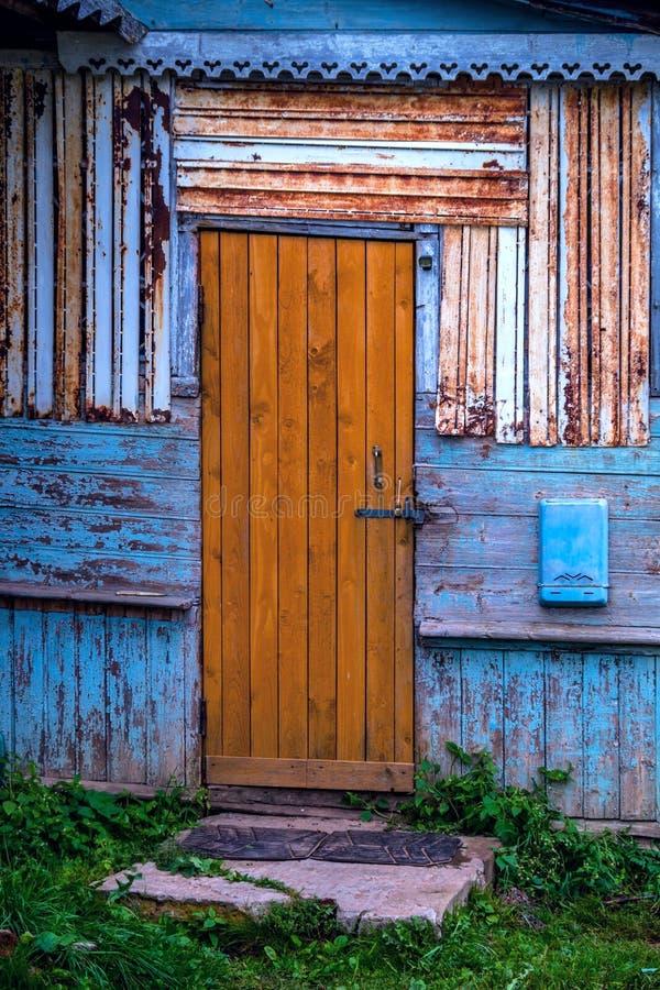 Imagem de fundo do estilo do Grunge, porta marrom de madeira velha em uma parede gasto azul de contraste imagens de stock royalty free