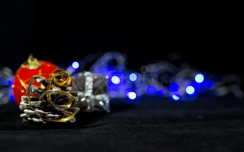 Imagem de fundo do Natal, bola vermelha no fundo borrado, luzes azuis, foco no cone do pinho imagem de stock royalty free