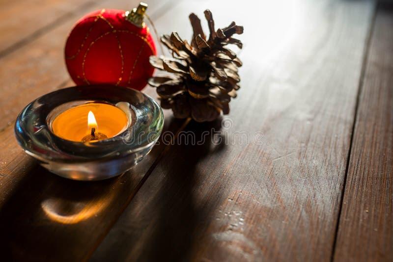 Imagem de fundo simples do Natal, luz natural entrando, cone do pinho, bola vermelha, foco na vela foto de stock