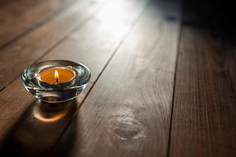 Imagem de fundo simples do Natal, vela de queimadura no fundo de madeira, luz natural entrando imagem de stock