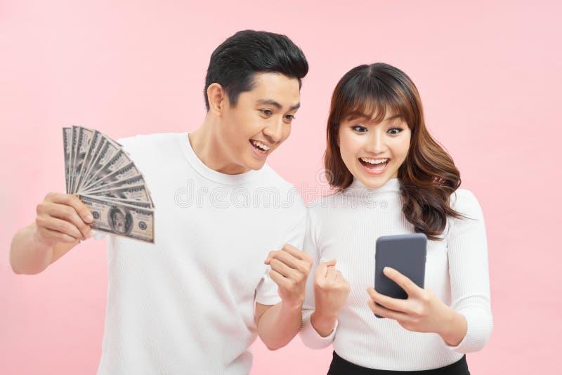 Imagem de jovem e animado casal asiático isolado sobre o fundo rosa de parede segurando dinheiro e telefone celular foto de stock royalty free
