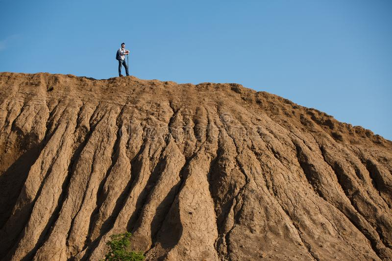 Imagem de longe do turista masculino com as varas para andar no monte contra o céu azul imagens de stock