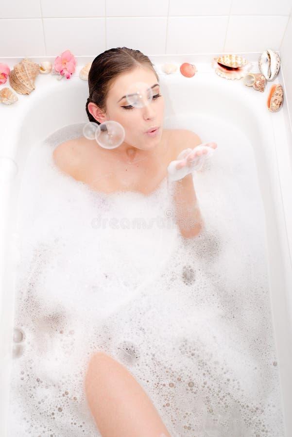 Imagem de relaxar a jovem mulher bonita que encontra-se em um banho dos termas com bolhas de sabão de sopro da espuma e do shell foto de stock royalty free