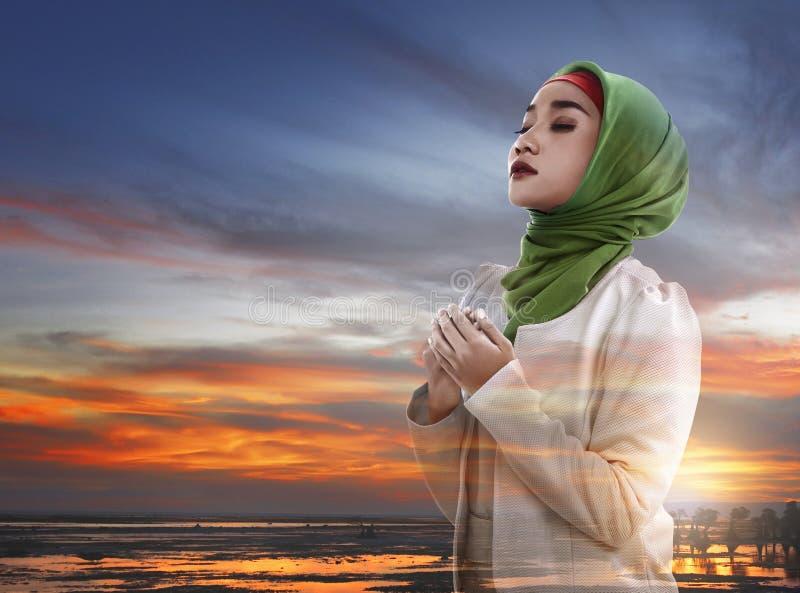 Imagem de rezar muçulmano da mulher da exposição dobro fotos de stock
