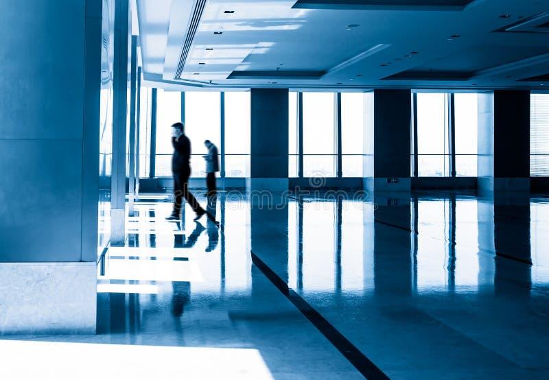 A imagem de silhuetas dos povos em morden o prédio de escritórios imagens de stock royalty free