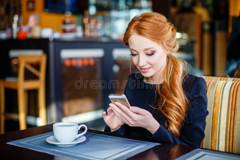 Imagem de sms fêmeas novos da leitura no telefone no café fotos de stock