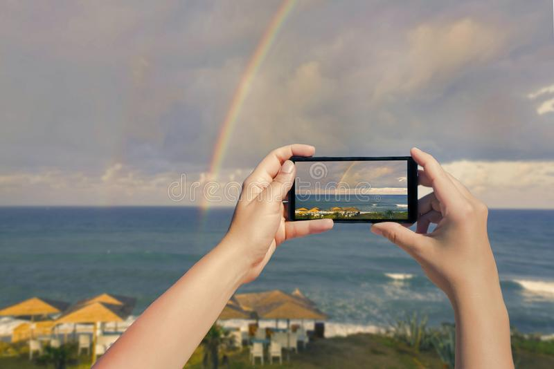 Imagem de tomada fêmea no telefone celular do arco-íris dobro sobre o oceano e da praia tropical com cadeiras e tabelas dos guard imagem de stock