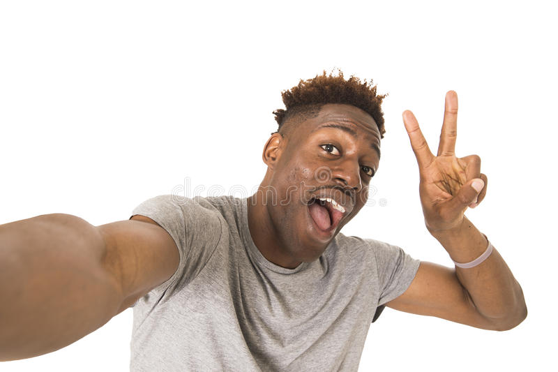 Imagem de tomada feliz de sorriso do autorretrato do selfie do homem afro-americano novo com telefone celular imagens de stock