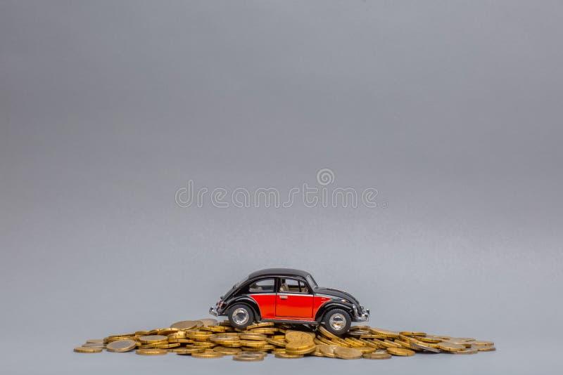 Imagem de um carro de Crimson colocada sobre um grande monte de moedas, sobre fundo cinza imagens de stock