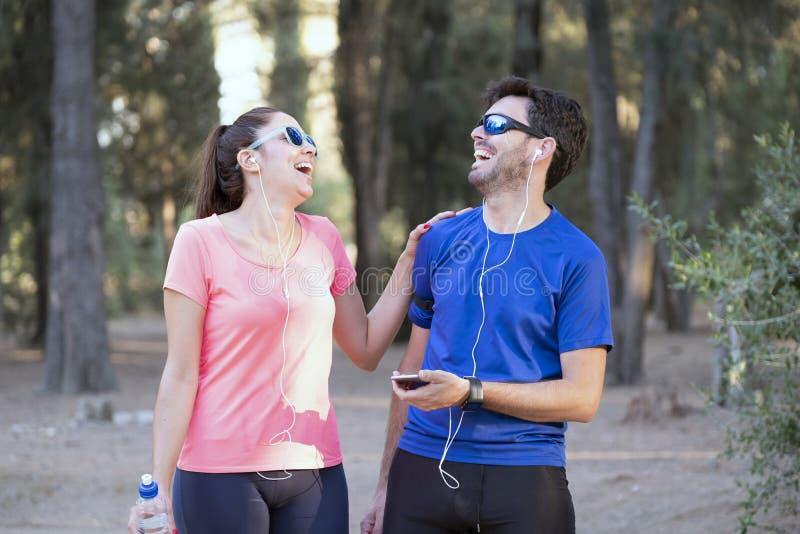 Imagem de um homem e mulher entusiasmados com fones de ouvido ouvindo música em celulares no parque imagem de stock royalty free