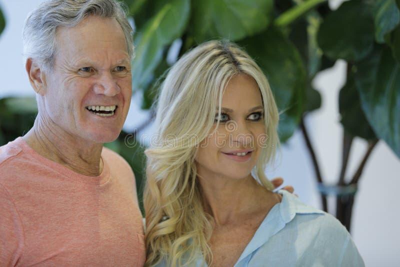 Imagem de um homem maduro e de uma esposa mais nova que sorriem fora da câmera imagem de stock royalty free