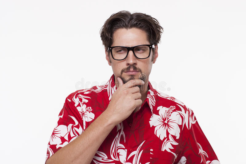 Imagem de um homem novo na camisa havaiana que levanta com mão no queixo fotos de stock royalty free