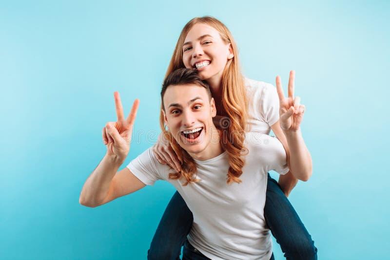 A imagem de um par de amor, com prazer, um homem leva uma mulher alegre no seu para trás, em um fundo azul foto de stock royalty free