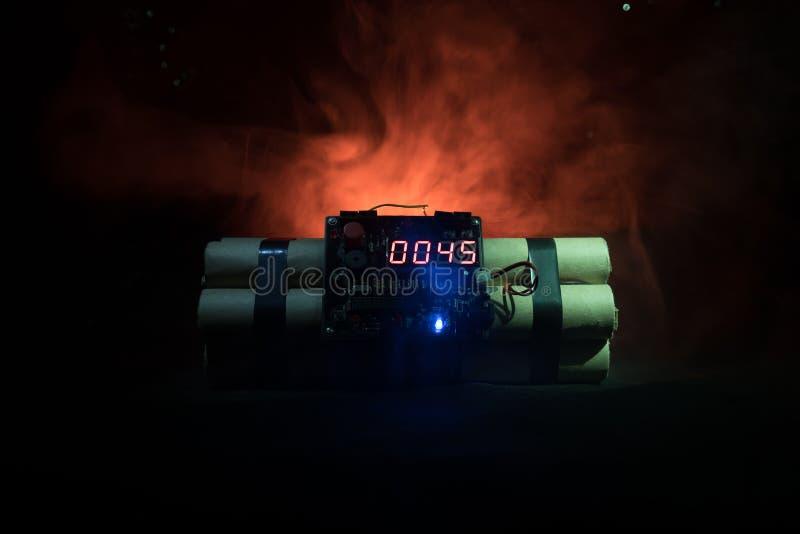 Imagem de uma bomba-relógio contra o fundo escuro Temporizador que conta para baixo à detonação iluminada em um brilho claro do e fotografia de stock royalty free